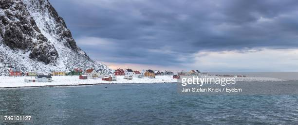 Houses On Snow Covered Field By Lake Against Sky