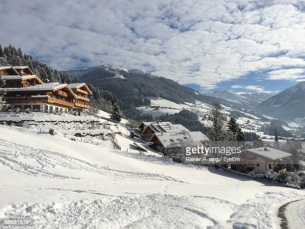 Houses On Snow Covered Field By Mountains Against Cloudy Sky