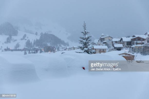 Houses On Snow Covered Landscape Against Sky