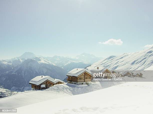 Houses On Snow Covered Mountains Against Sky