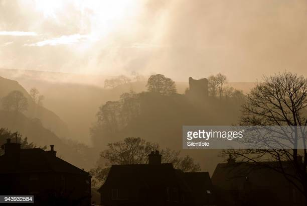 houses rooftops afore misty landscape with english castle - peveril castle stock pictures, royalty-free photos & images