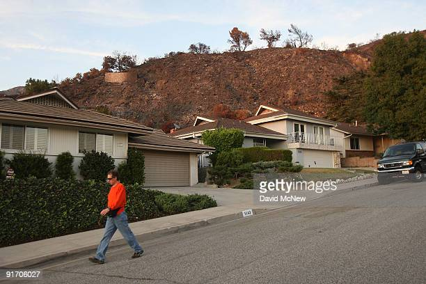 Houses stand below charred hills as residents prepare in advance of the first rain since before the massive Station fire started for the possible...