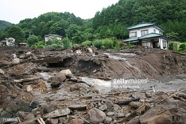 Houses stand damaged after heavy rain and a mudslide hit Okaya city July 20, 2006 in Nagano, Japan. Torrential rains in central and western Japan...