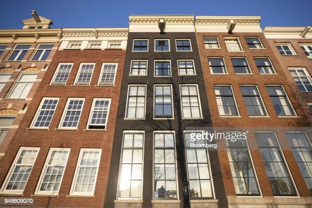 Houses stand near the river Amstel in Amsterdam Netherlands on Friday April 20 2018 Brexit will lead as many as 30 significant financial firms to...