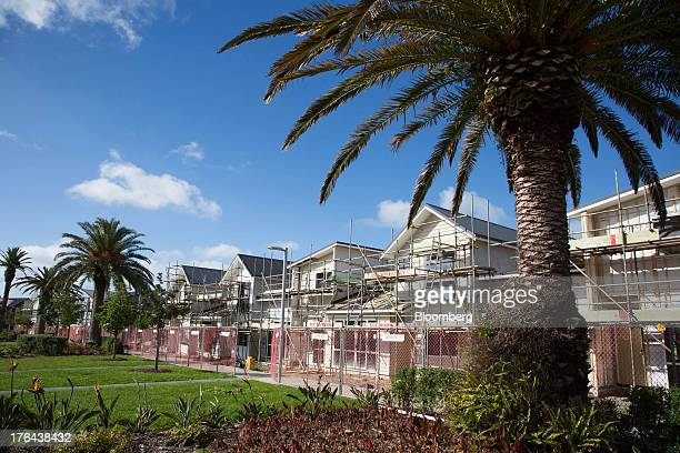 Houses stand under construction behind palm trees in the suburb of Hobsonville Point in Auckland New Zealand on Tuesday Aug 13 2013 New Zealand's...