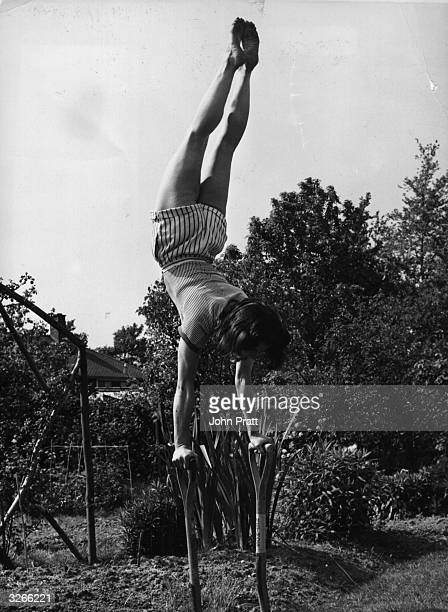 Housewife and former acrobat Mrs Jacqueline Sawyer engages in a bit of impromptu gymnastics in her back garden using a pair of spades for support
