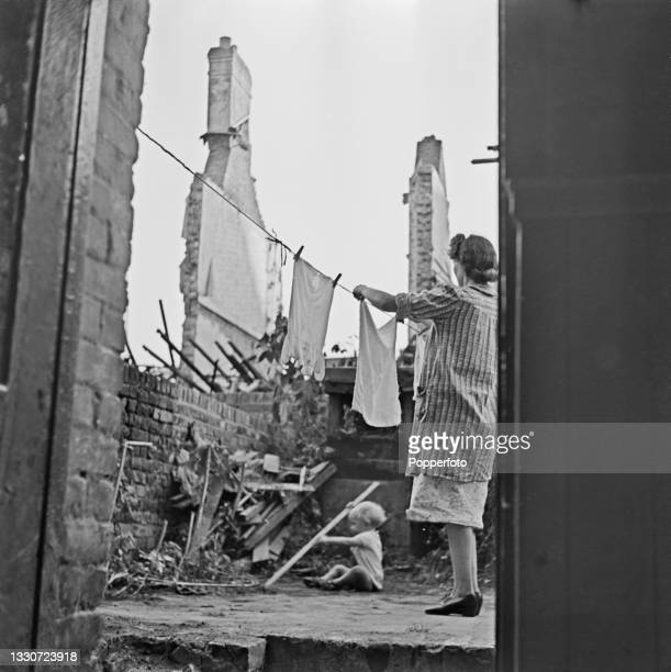 Housewife and mother hangs out washing on a line as a toddler plays on the ground in the garden of a blitzed and bomb damaged house in England during...