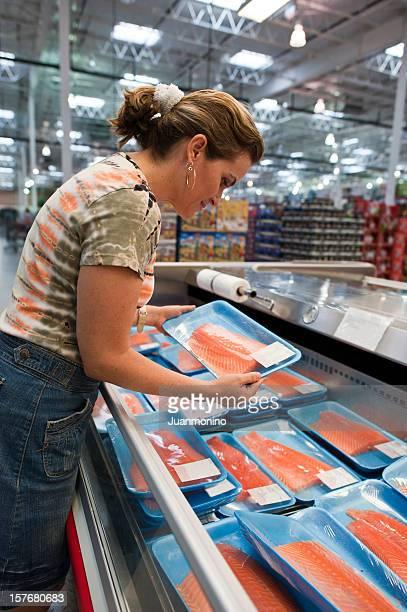 Femme achète un plateau de saumon frais