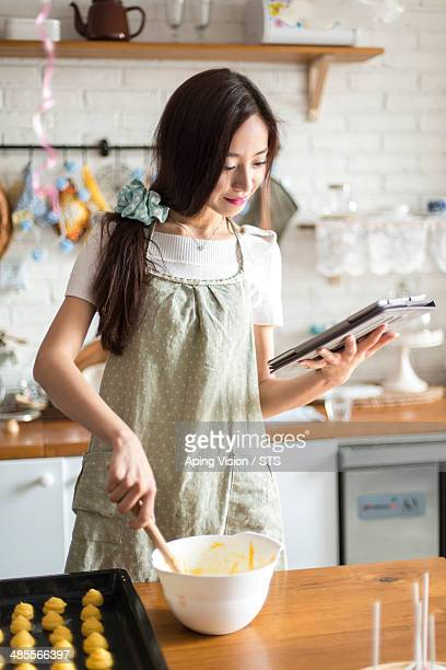 housewife cooking while checking digital tablet