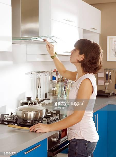 housewife cooks in the kitchen - afzuigapparaat stockfoto's en -beelden