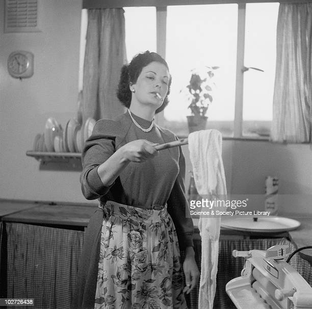 Housewife doing the laundry whilst smoking 1954 Housewife doing the laundry whilst smoking 1954 Photograph by British Transport Films photographer...