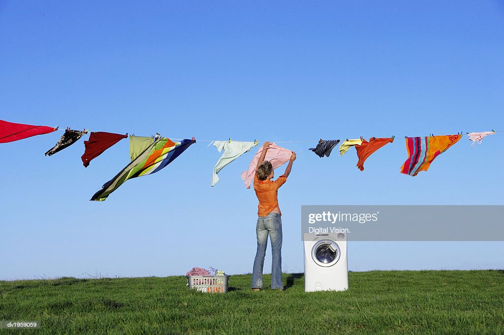 Housewife Hanging Laundry on a Washing Line Standing by a Washing Machine : Stock Photo