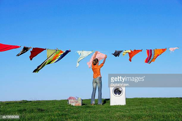 housewife hanging laundry on a washing line standing by a washing machine - 物干し ストックフォトと画像