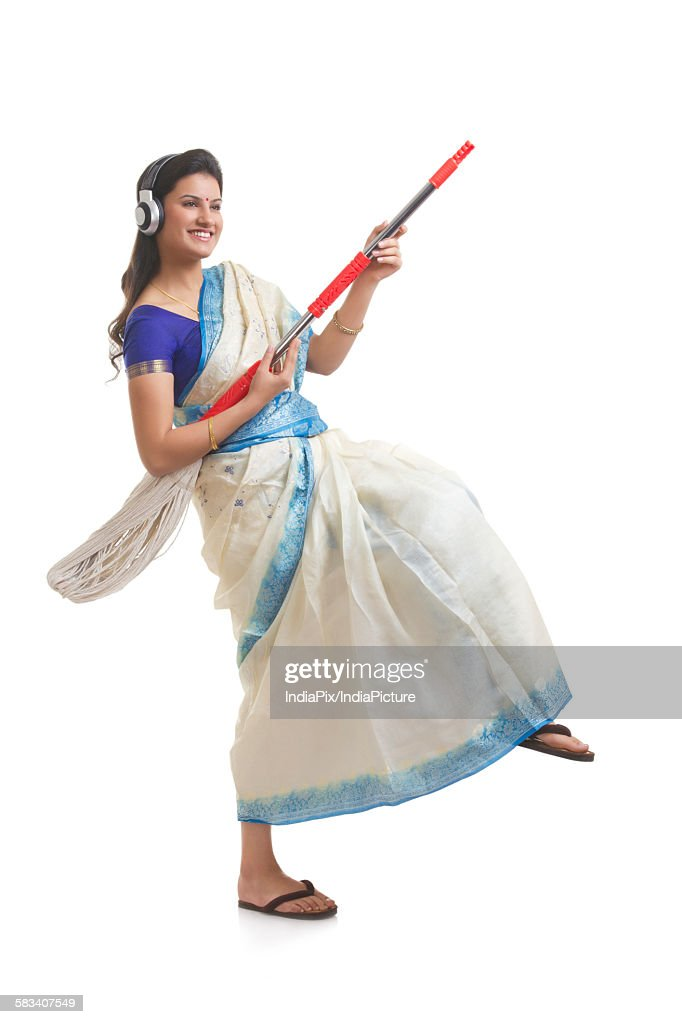 Housewife having fun while listening to music : Stock Photo
