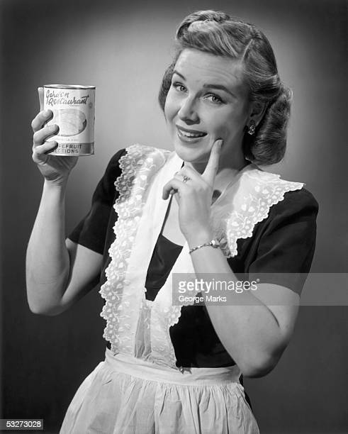Housewife in apron holding a can of fruit