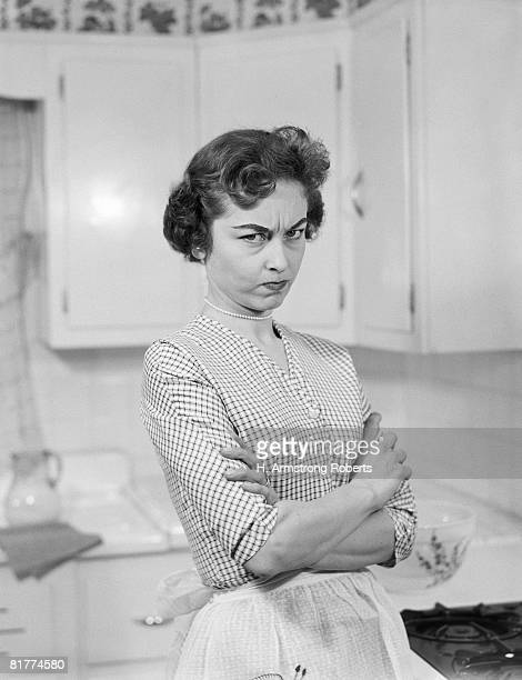 Housewife in kitchen, arms folded, with serious expression.