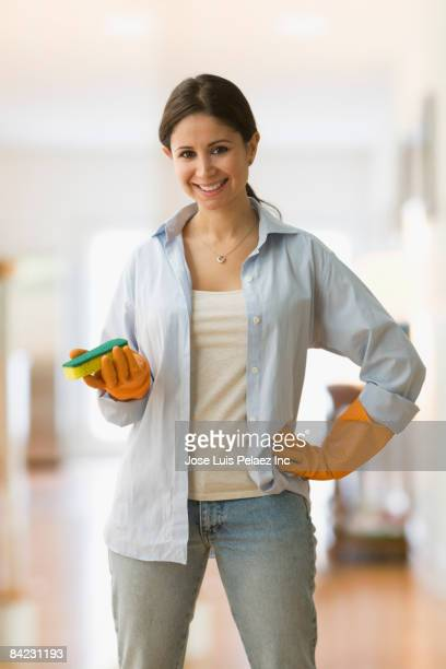 Housewife in rubber gloves holding sponge