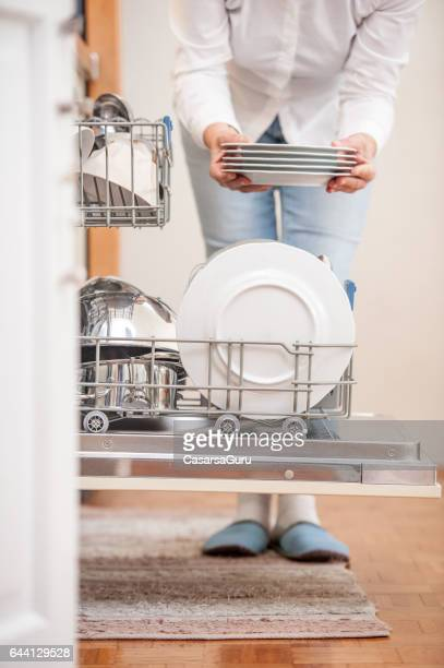 Housewife In The Kitchen Unloading Plate From Dishwasher