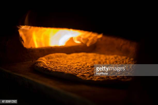 A housewife is making traditional Lezgi bread in Khazra village Qusar district Azerbaijan on 6 October 2016 She prepares dough from flour water and...