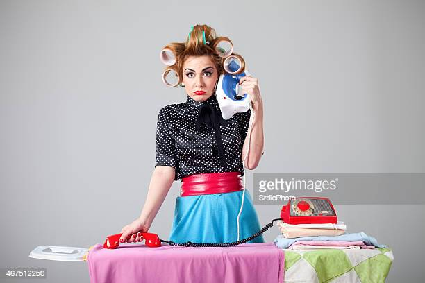 Housewife making phone call with iron