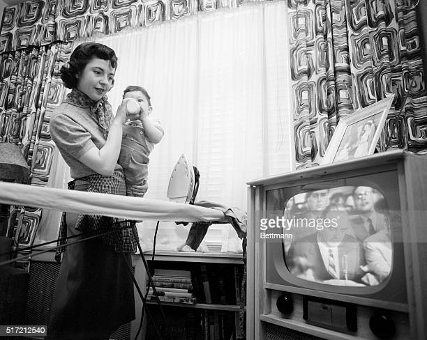 Housewife Marie Breetveld holds her son while watching the televised McCarthyArmy hearings on April 22 1954