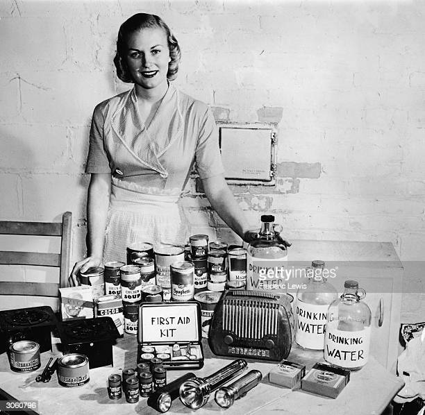 A housewife model smiles while posing with a display of bomb shelter supplies during the Cold War 1950s