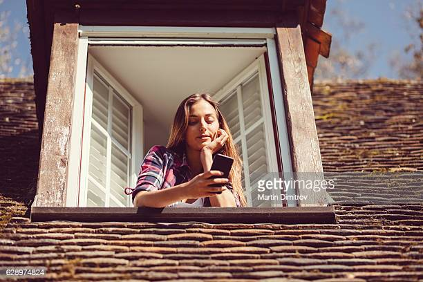 Housewife on the window using smartphone