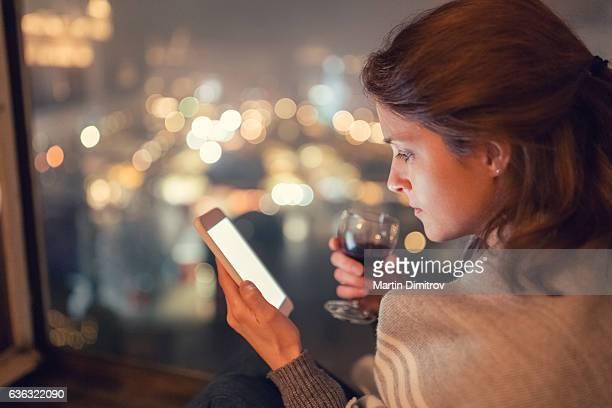 Housewife on the window using smartphone
