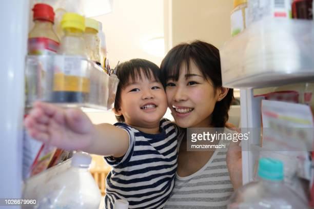 主婦は彼女の腕の中で幼児と冷蔵庫のドアを開ける - 冷蔵庫 ストックフォトと画像