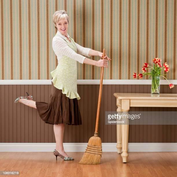 Hausfrau posieren mit Besen