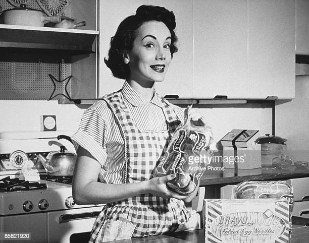 A housewife prepares a meal using sliced bread and Bravo egg noodles circa 1950