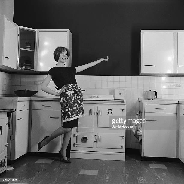 A housewife proudly displays her new fitted kitchen and Rayburn aga circa 1960 A photoshoot for Rayburn