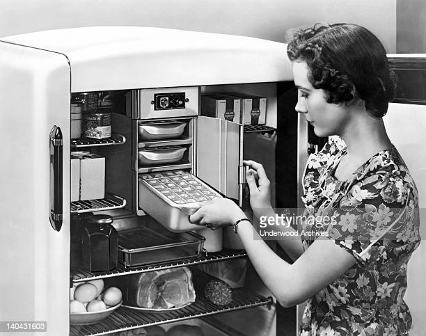 A housewife puts an ice cube tray into the freezer section of her refrigerator United States circa 1945