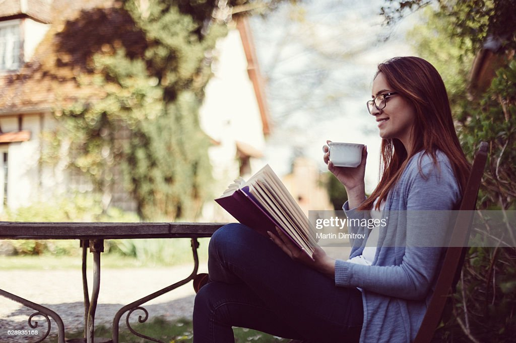Housewife reading a book at the veranda : Stock Photo