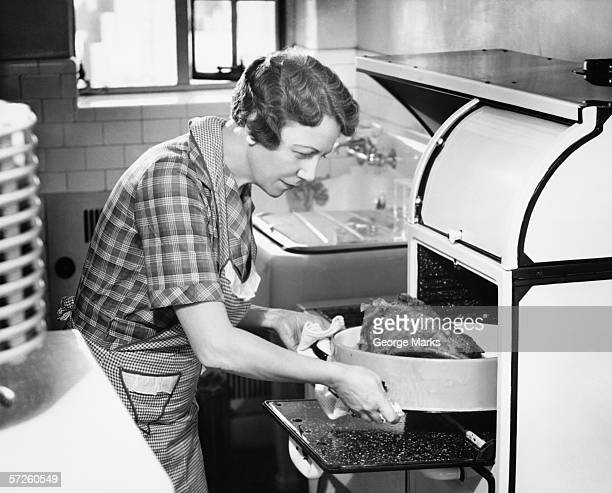 housewife removing turkey from oven, (b&w) - 20th century stock pictures, royalty-free photos & images