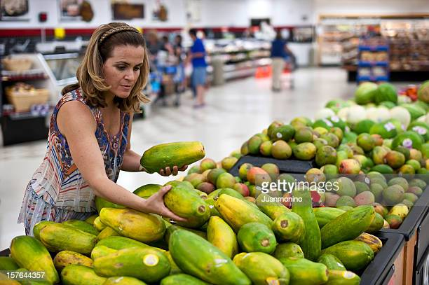 housewife shopping for papayas - papaya stock photos and pictures