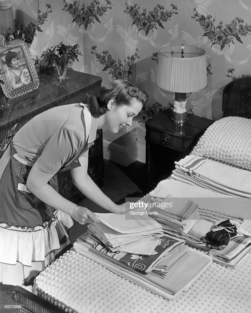 Housewife sorting ironed linens & towels : Stock Photo