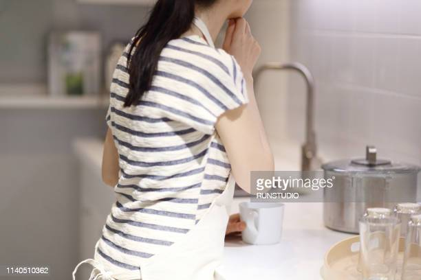 housewife standing with hand on chin in kitchen - 台所 ストックフォトと画像