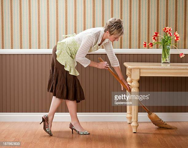Housewife Sweeping Under Table