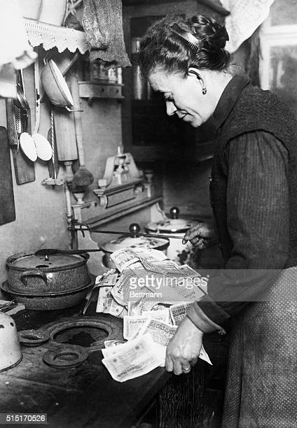 A housewife uses millions of deutsche marks to light a stove during a period of hyperinflation in Germany