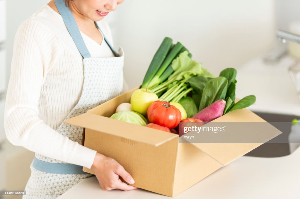 Housewife with cardboard box containing various vegetables : Stock Photo