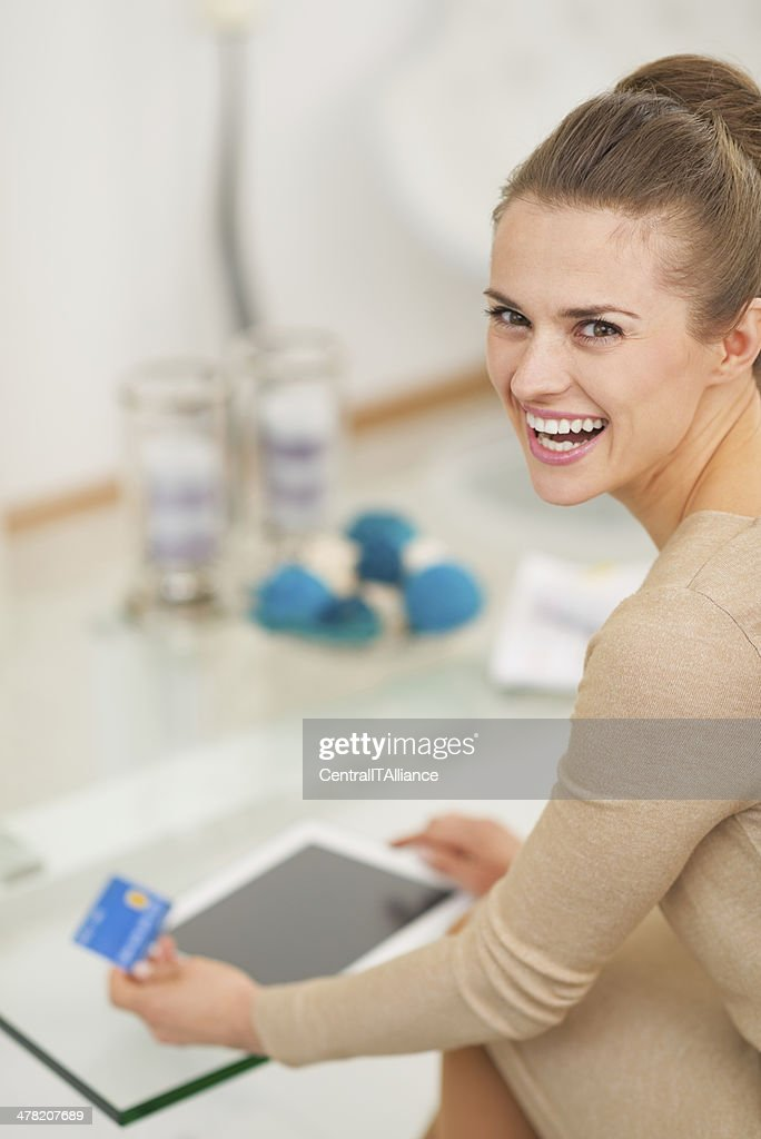 housewife with credit card using tablet pc in living room stock