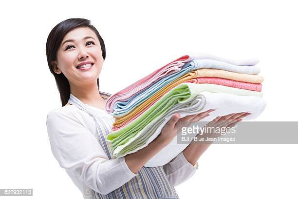 Housewife with stack of clean towels