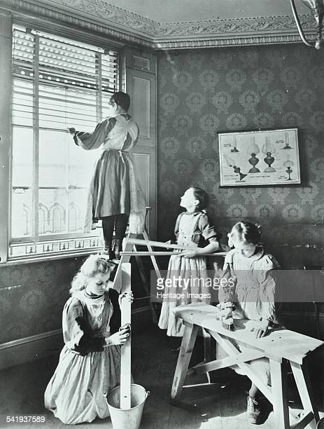 Housewifery lesson Dulwich Hamlet School Dulwich Village London 1908 Four schoolgirls are busy taking the slats out of venetian blinds and cleaning...