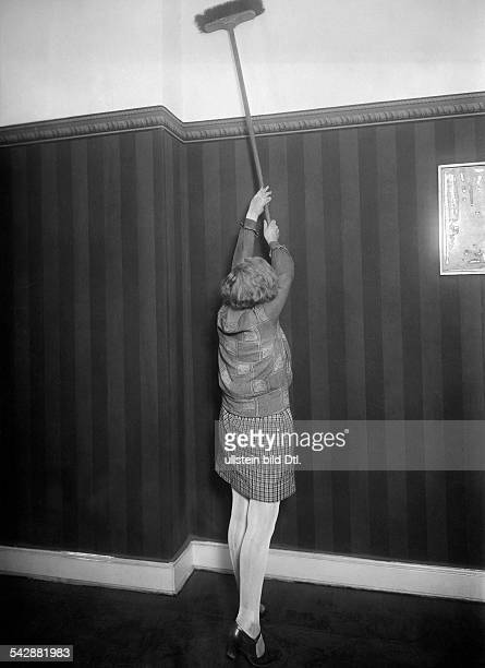 Housewives household chores A woman cleaning the upper part of a wall with a broom 1927 Vintage property of ullstein bild