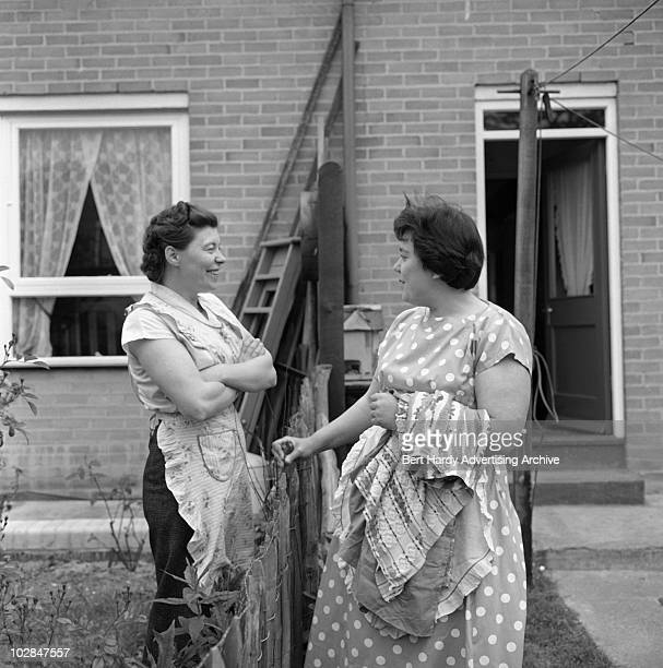 Housewives Mrs Thorn and Mrs Jackson chatting over their garden fence 28th May 1960