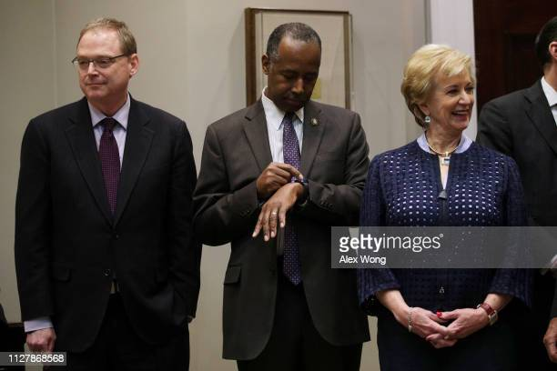 Housing and Urban Development Secretary Ben Carson looks at his watch as he waits with Small Business Administration Administrator Linda McMahon and...