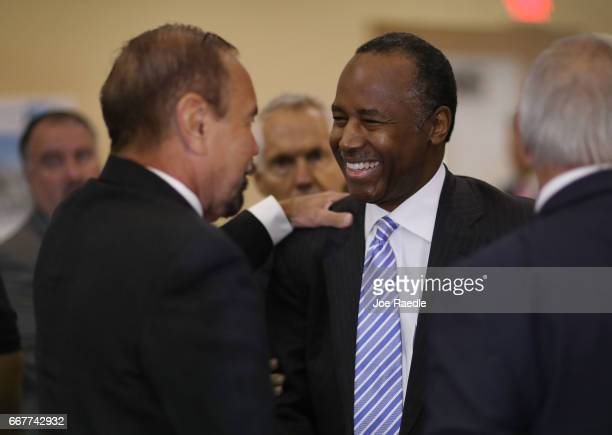 S Housing and Urban Development Secretary Ben Carson speaks with Jorge Perez CEO Related Urban Group during a visit to the Liberty Square apartment...