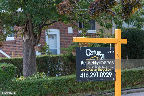 Housing Market Century 21 realtor board with a forsale sign hung on a sign post in front of a small garden and a residential house