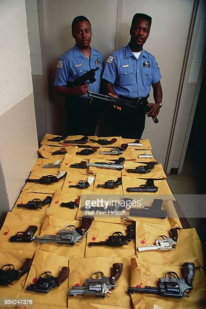 Housing police officers pose with a collection of guns confiscated in and around public housing in Chicago